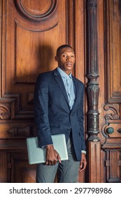 African American businessman working in New York. Wearing black blazer, carrying laptop computer,  a school teacher standing by vintage style classroom, confidently looking forward. Graduate Student.