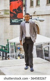 African American Businessman working in New York. Wearing gray blazer, bow tie, black pants, leather shoes, holding laptop computer, a college student standing on Wall Street, looking forward.