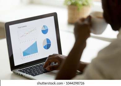 African american businessman working with project statistics on laptop screen, analyzing financial graphs and charts, using business software application for data analysis concept, close up rear view