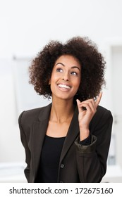 African American businesswoman with a bright idea smiling with glee and raising her finger as she has a brainwave and realizes the solution to a problem