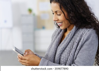 African American businesswoman checking her mobile phone for messages reading an sms with a pleased smile, side view close up in the office