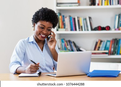 African american businesswoman with computer at phone at office at home