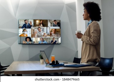 African American businesswoman looking at projection screen while talking to group of coworkers through conference call in the office.