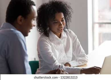 African American businesswoman mentor helping male trainee with online project or new software, using laptop together, looking at screen, staff training, colleagues working together, teamwork concept