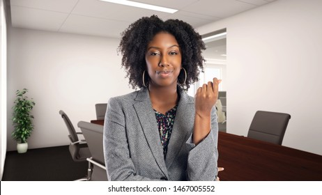 African American businesswoman in an office doing a money gesture.  She is an owner or an executive of the workplace.  Depicts careers and startup business.