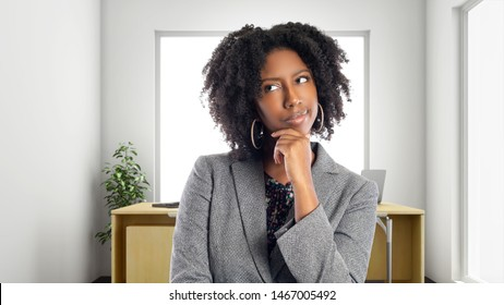 African American businesswoman in an office thinking of ideas.  She is an owner or an executive of the workplace.  Depicts careers and startup business.