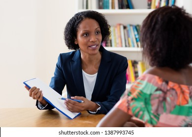 African american businesswoman showing contract to apprentice at job interview with applicant at office