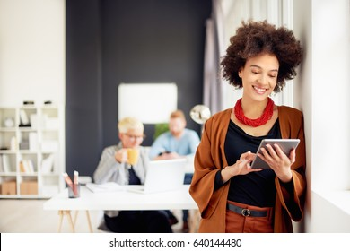 African american businesswoman standing in modern office and using tablet device. Beside her colleagues