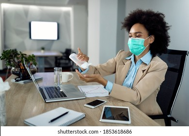 African American businesswoman using hands sanitizer and wearing face mask while working in the office during coronavirus pandemic.