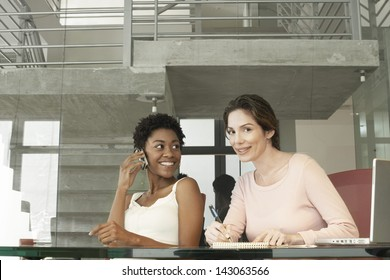 African American businesswoman using mobile phone while female colleague writing on notepad in office