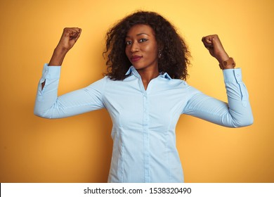 African american businesswoman wearing elegant shirt over isolated yellow background showing arms muscles smiling proud. Fitness concept.