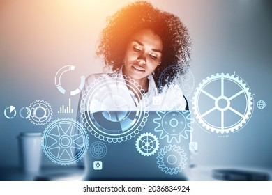 African American businesswoman wearing white shirt is typing on laptop with digital hologram with cogwheels, icons of padlock, globe, human, bar and pie diagrams. Office workplace in background