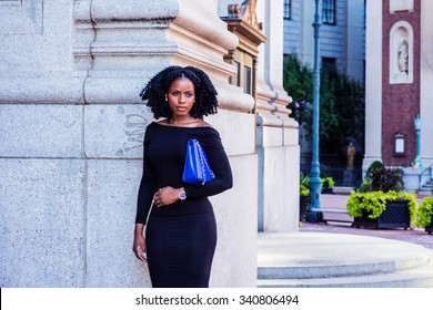 African American Businesswoman working in New York. Wearing long sleeve, off shoulder dress, carrying bag under arm, a lady with braid hairstyle standing on street. Filtered look with purple tint.