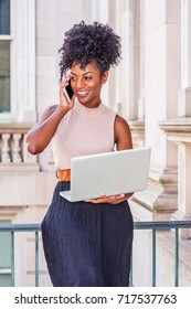 African American Businesswoman working in New York. Young black college student with afro hairstyle sitting on railing in vintage style office building, working on laptop computer, making phone call.