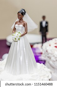An African American cake topper bride and groom in the back ground