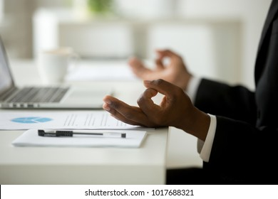 African american calm businessman relaxing meditating in office, peaceful ceo in suit practicing yoga at work, focus on black man hands in mudra, successful mindful people habits concept, close up