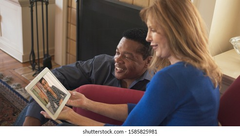 African American and Caucasian couple video chatting with daughter on tablet computer. Older couple facetiming on tablet computer with daughter