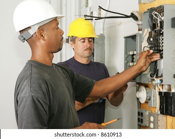 An african american and a caucasian electrician working on a panel.  Actual electricians performing work according to industry safety and code standards.