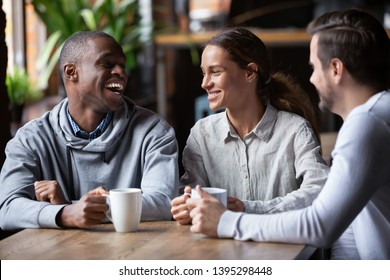 African American and Caucasian friends having fun together in coffeehouse, diverse people chatting, laughing at joke, discussing good news at coffee break, having pleasant conversation