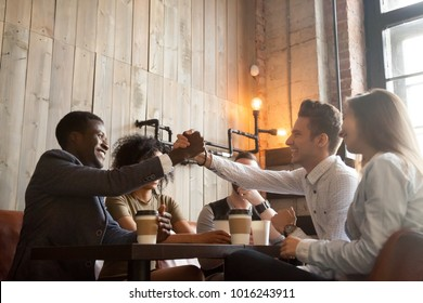 African american and caucasian men shaking hands at coffeehouse meeting with diverse friends, multiracial smiling male buddies greeting with friendship handshake sitting sharing table in cozy cafe
