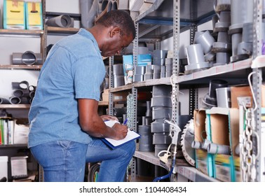 African American  cheerful positive salesman checking goods availability on shelves of building materials shop