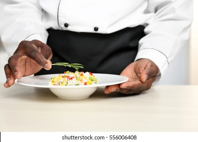African American chef adding rosemary to tasty salad in kitchen, closeup