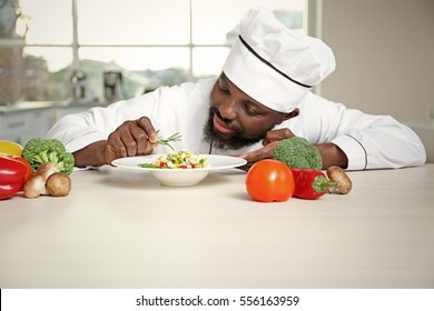 African American chef cooking tasty salad in kitchen