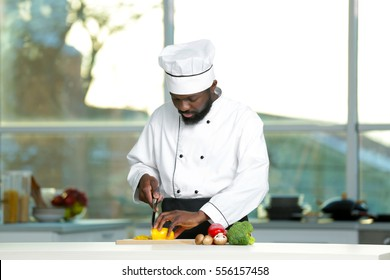 African American chef cutting vegetables in kitchen