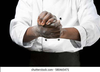 African American chef with flour on dark background, closeup