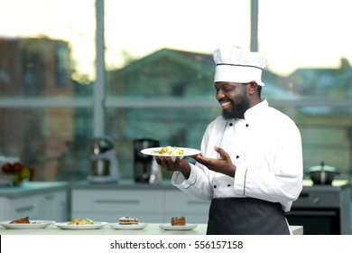 African American chef with plate of tasty salad in kitchen