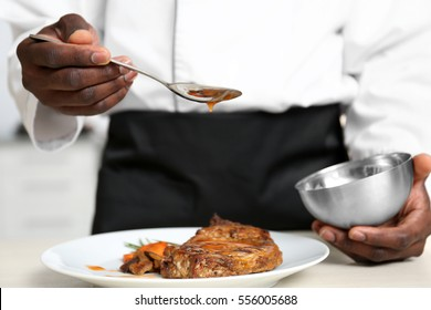 African American chef pouring sauce on tasty meat in kitchen, closeup