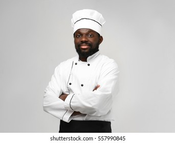 African American chef in uniform on light background