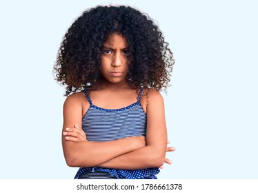 African american child with curly hair wearing swimwear skeptic and nervous, disapproving expression on face with crossed arms. negative person.