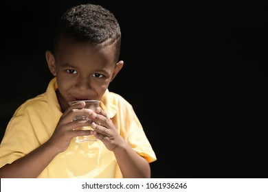 African American child drinking water on dark background. Water scarcity concept