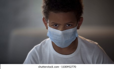 African American child in medical mask looking in camera with sad eyes, epidemic