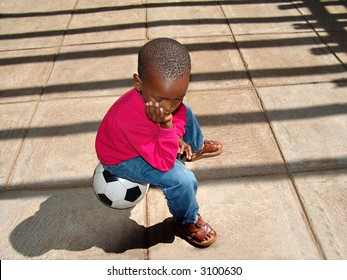 African American child sitting on the ball waiting for his friends at school for a soccer game.