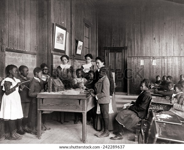 African American children learning about Thanksgiving, with model log cabin on table, Whittier Primary School, Hampton, Virginia. Ca. 1899.