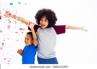 African American children smiling with happiness throwing colorful confetti. Friendship, siblings, celebration concept