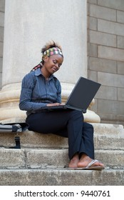 African American college student with laptop on library steps