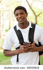 An African American College student smiling holding school supplies