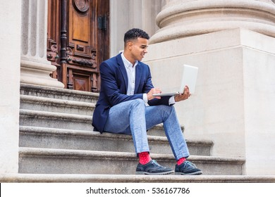 African American college student studying in New York, wearing blazer, gray pants, red socks, sneakers, sitting on stairs outside office building, working on laptop computer. Color filtered effect