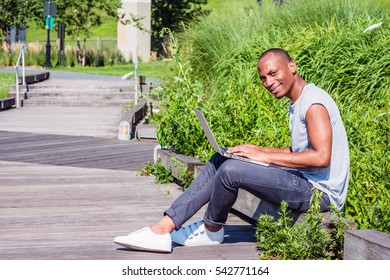 African American College Student studying in New York, wearing T shirt, black jeans, white sneakers,, sitting on wooden road on campus, working on laptop computer, smiling. Color filtered effect