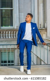 African American college student studying in New York, wearing blue suit, white collarless shirt, sneakers, sitting on railing in vintage office building on campus, taking break, looking up, thinking.