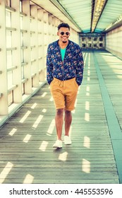 African American college student, wearing blue patterned jacket, yellow brown shorts, white sneakers, sunglasses, walking on walkway with glass walls, ceiling, wooden floor on campus in New York.