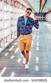 African American college student, wearing blue patterned jacket, yellow brown shorts, white sneakers, sunglasses, walking on walkway with glass walls on campus in New York. Color filtered effect