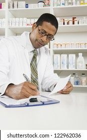 African American confident pharmacist writing prescription with medicines in the background