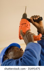 African American Construction Worker, Handyman, Carpenter, Drilling with Electrical Power Tool