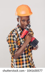African American construction worker in helmet uses electric screwdriver