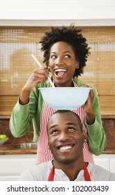 African American couple baking in kitchen