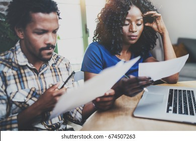 African american couple checking home bills together at the wooden table.Young black man and his girlfriend using laptop while working at home in the living room.Horizontal,blurred background.Cropped
